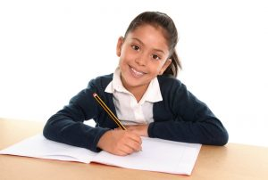 Happy little hispanic female child writing homework with pencil smiling in children education and back to school concept isolated on white background